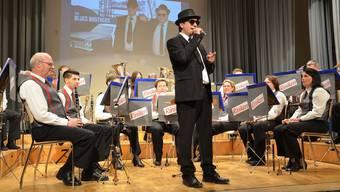 Als cooler Blues Brother eröffnet Dirigent Rafal Jastrzebski mit der MG Riniken den Konzert- und Filmabend.