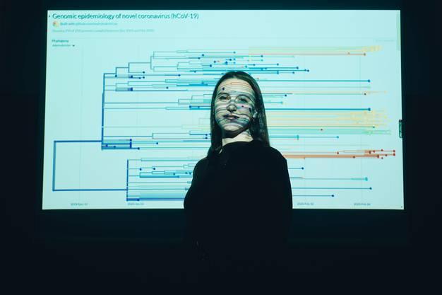 Emma Hodcroft im Biozentrum der Universität Basel: Sie steht in einer Projektion des Coronavirus-Stammbaums.