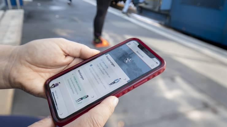 Eine Frau nutzt die SwissCovid Contact Tracing App auf ihrem Smartphone. (KEYSTONE/Gaetan Bally)