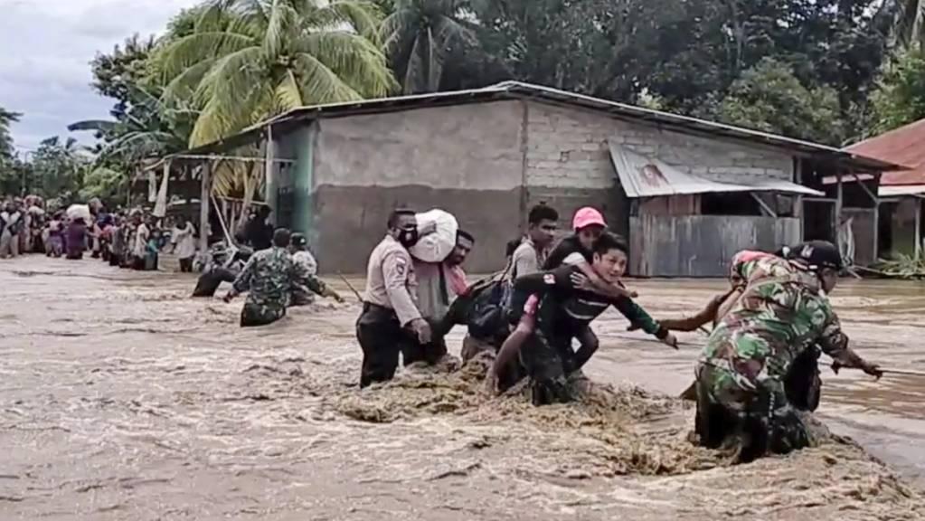 Soldaten und Polizisten helfen Anwohnern über eine überflutete Straße. Foto: Uncredited/AP/dpa