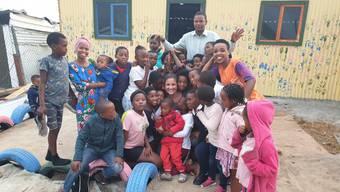 Tabea Pusceddu umgeben von Kindern und Betreuern bei einem Besuch im Township Zwelihle in Hermanus.
