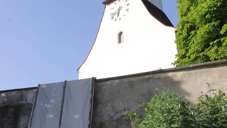 Die Mauer vor der reformierten Dorfkirche in Bözen ist brüchig und musste mit Sofortmassnahmen gegen die Witterung geschützt werden.