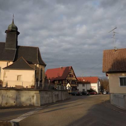 Hunkeler auf der Fahrt ins Elsass, die gotische Kirche von Knoeringe, ein Riegelhaus und dahinter die Beiz Stoller, in die Hunkeler regelmässig einkehrt.