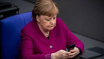 Kanzlerin Angela Merkel im Bundestag mit ihrem Handy.