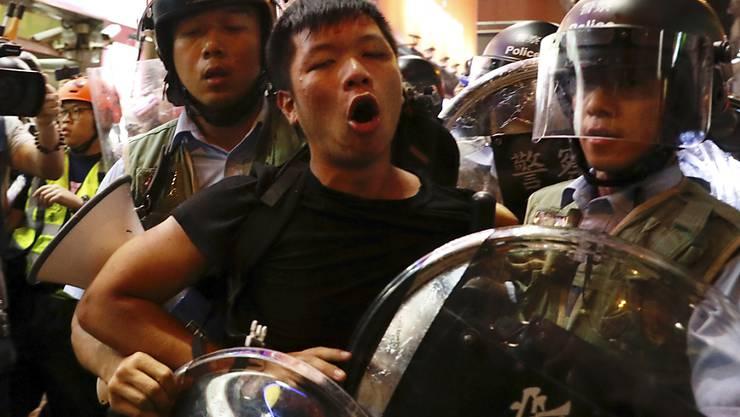 Polizisten in Hongkong führen am Sonntag einen Demonstranten ab.
