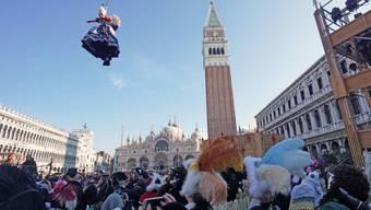 """Der traditionelle """"Engelsflug"""" hat am Sonntag den Karneval von Venedig eingeläutet. Dabei gleitet eine Frau an einem Stahlseil vom 97 Meter hohen Campanile des Markusdoms auf den Markusplatz herab."""