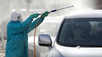 Ein Beamter desinfiziert ein Auto in der Nähe einer wahrscheinlich von der Vogelgrippe betroffenen Hühnerfarm.