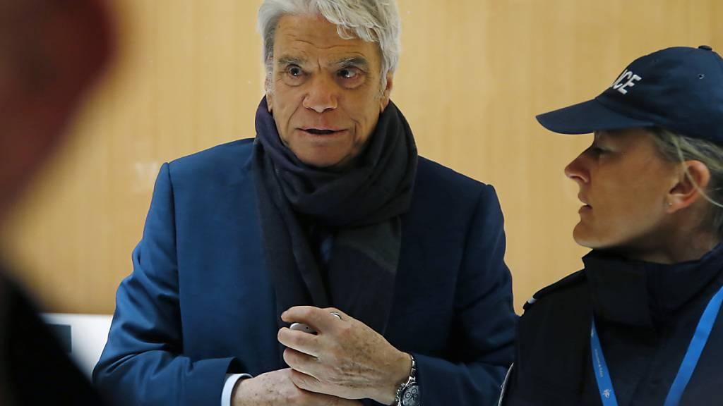 ARCHIV - Bernard Tapie (l), französischen Manager, Ex-Minister, Schauspieler und Fußballmanager, kommt in Begleitung einer Polizistin an einem Pariser Gericht an. Ein brutaler Einbruch bei Tapie sorgt für Entsetzen in Frankreich. Foto: Michel Euler/AP/dpa