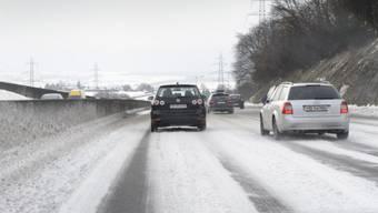 Autos fahren auf der schneebedeckten Umfahrung von Lausanne.