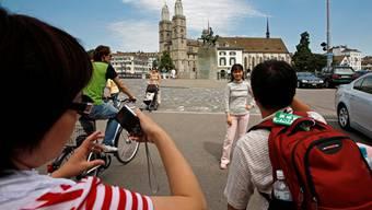 ACHTUNG REDAKTIONEN ? ZUR SCHWEIZER FREMDENVERKEHRSBILANZ 2009 STELLEN WIR IHNEN FOLGENDES THEMENBILD ZUR VERFUEGUNG --- Touristen besuchen die Zuercher Altstadt mit dem Grossmuenster, hinten, am Montag, 13. Juli 2009 in Zuerich. (KEYSTONE/Alessandro Della Bella)
