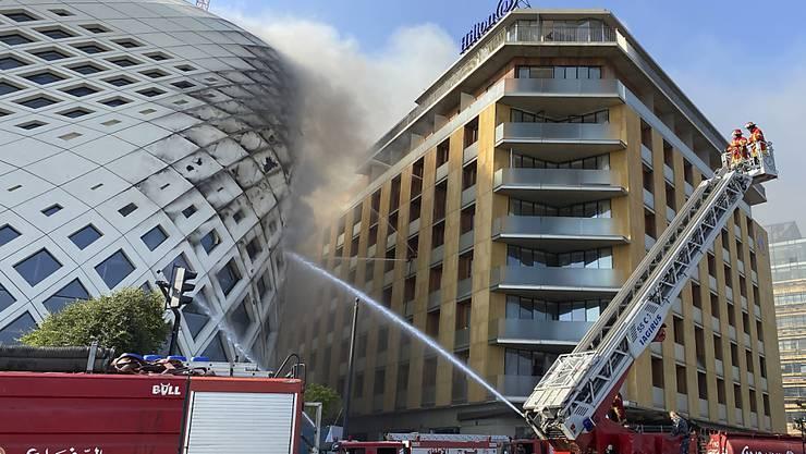 Feuerwehrleute löschen einen Brand im Geschäftsviertel der libanesischen Hauptstadt. Betroffen ist das sich noch im Bau befindlichen Gebäude (l), das von der Architektin Zaha Hadid entworfen wurde. Foto: Fadi Tawil/AP/dpa