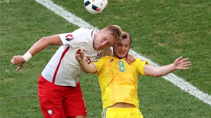 Roman Zozulya (rechts) und Kamil Glik köpfeln am EM-Spiel Ukraine gegen Polen um den Ball.