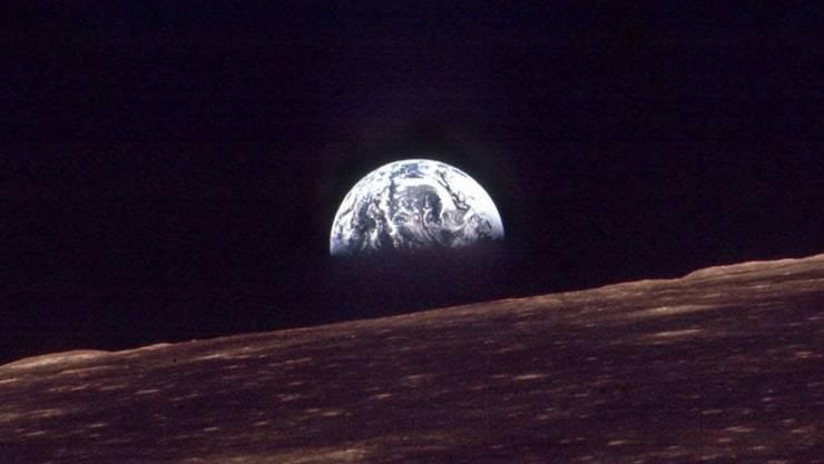 Die Erde, wie sie am 24. Dezember 1968 über dem Mondhorizont aufging, aufgenommen aus der Apollo 8. Deren Besatzung - Jim Lovell, Frank Borman und William Anders - waren die ersten Menschen, die Weihnachten im Weltall feierten, etwa 370 Kilometer über Meer. (Archivbild)
