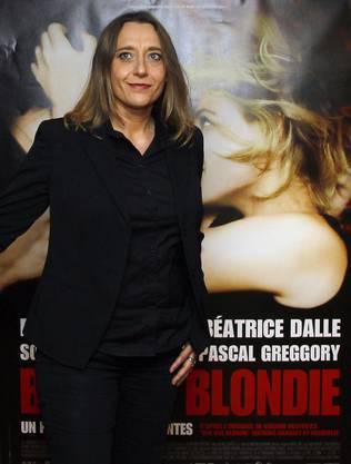 """Despentes vor einem Plakat ihres Films """"Bye Bye Blondie""""."""