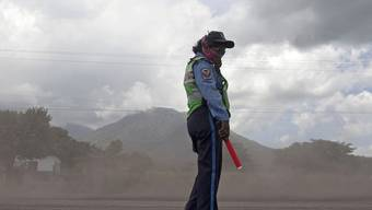 Polizistin steht im Ascheregen in der Nähe des Vulkans San Cristobal