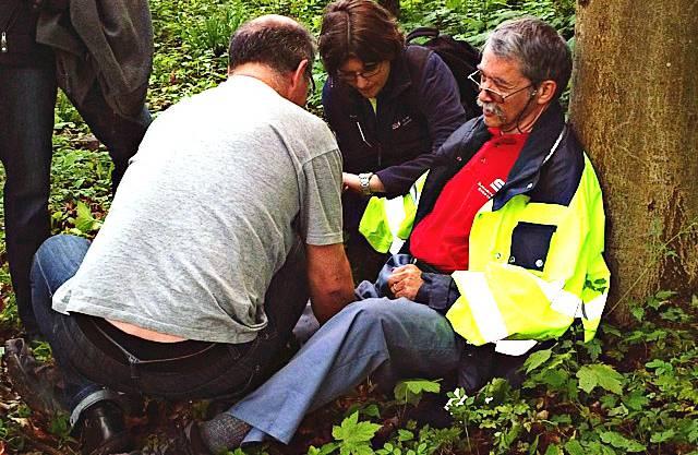 Dem Waldarbeiter wird der Puls genommen und die Arterie mit viel Druck abgebunden.