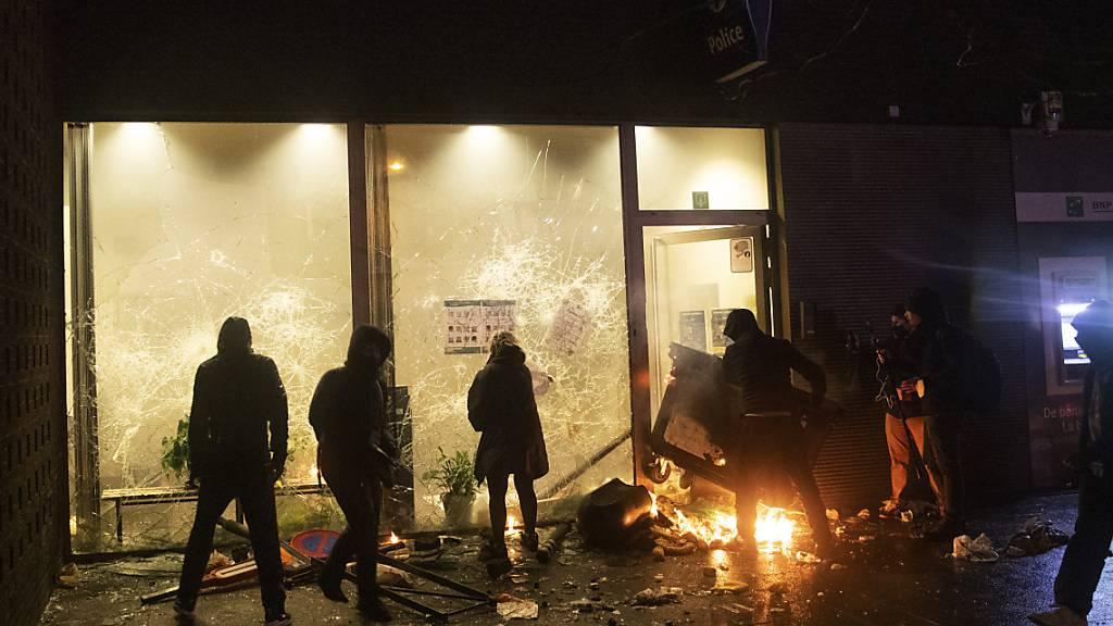Demonstranten stehen vor einem Polizeibüro in Brüssel. Die Proteste wurden vom Tod eines 23-jährigen Mannes ausgelöst, der letzte Woche in Brüssel von der Polizei festgenommen wurde. Foto: Francisco Seco/AP/dpa