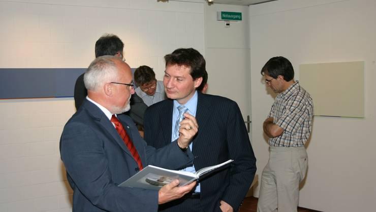 Spannende Lektüre: Stadtrat Gregor Tomasi (links) unterhält sich an der Vernissage mit dem neuen IBB-CEO Eugen Pfiffner über das Buch «Brugger Brunnen». (Louis Probst)