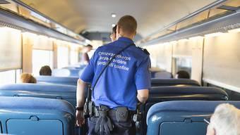 Kontrollieren nicht nur Reisende, sondern auch Bargeld: Schweizer Grenzwächter in einem Zug.