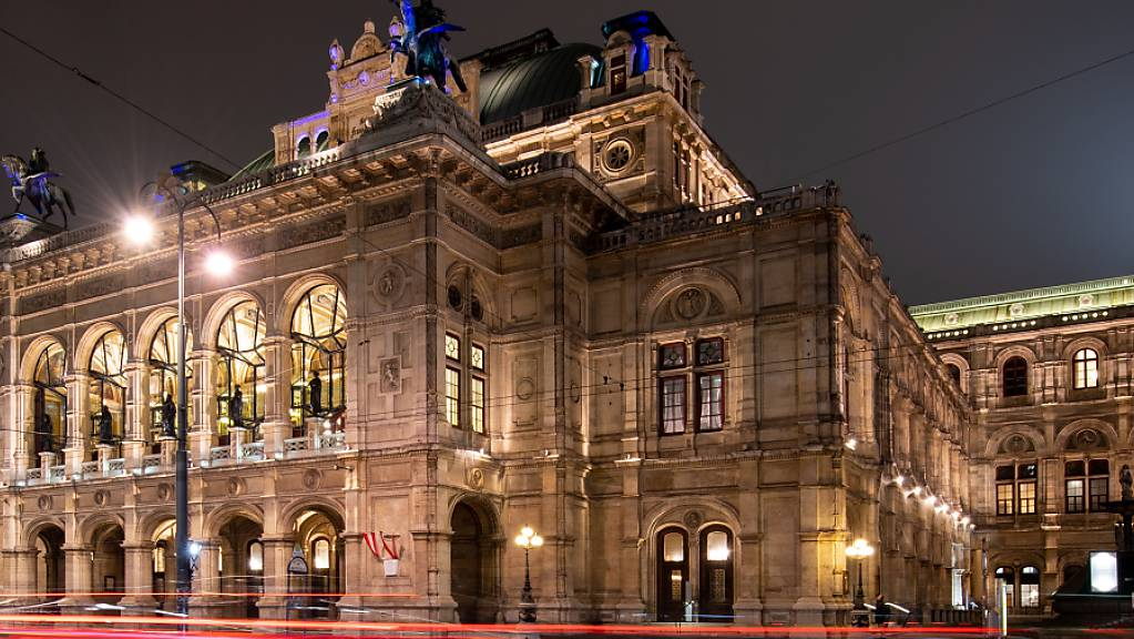 Lichter vorbeifahrender Autos vor der Wiener Staatsoper am Abend.