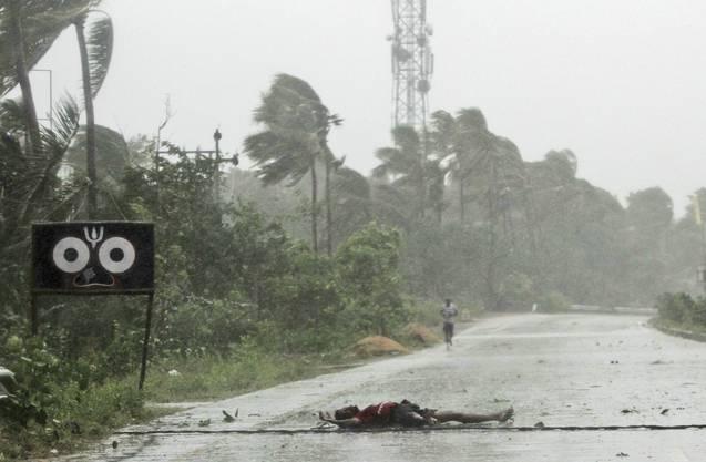 Mehr als eine Million Menschen waren zuvor nach Angaben der Regierung des Bundesstaates Odisha in Sicherheit gebracht worden. Der Mann im Bild wurde von der Wucht des Windes umgeblasen – aber er lebt.