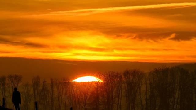 Die Sonne verschwindet hinter Hügeln im Jura