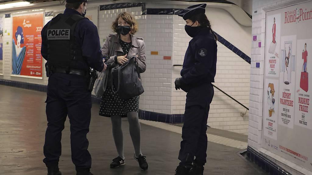 In einer U-Bahn-Station in Paris kontrollieren zwei Polizisten eine Pendlerin. Im Kampf gegen die Corona-Pandemie gelten in Frankreich weitreichende Ausgangsbeschränkungen. Foto: Thibault Camus/AP/dpa
