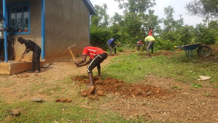 Arbeiter beginnen mit der Planierung des Bodens für das neue Schulzimmer