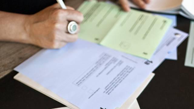 Eine Frau bei der brieflichen Stimmabgabe (Symbolbild)