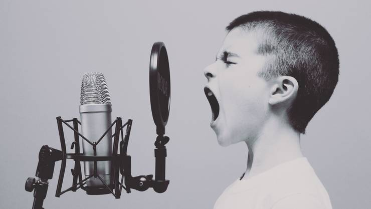 Junge schreit singt ins Mikrofon