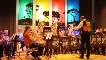 Die Musikgesellschaft Wölflinswil-Oberhof vor der Kulisse zum Motto «Jahreszeiten».