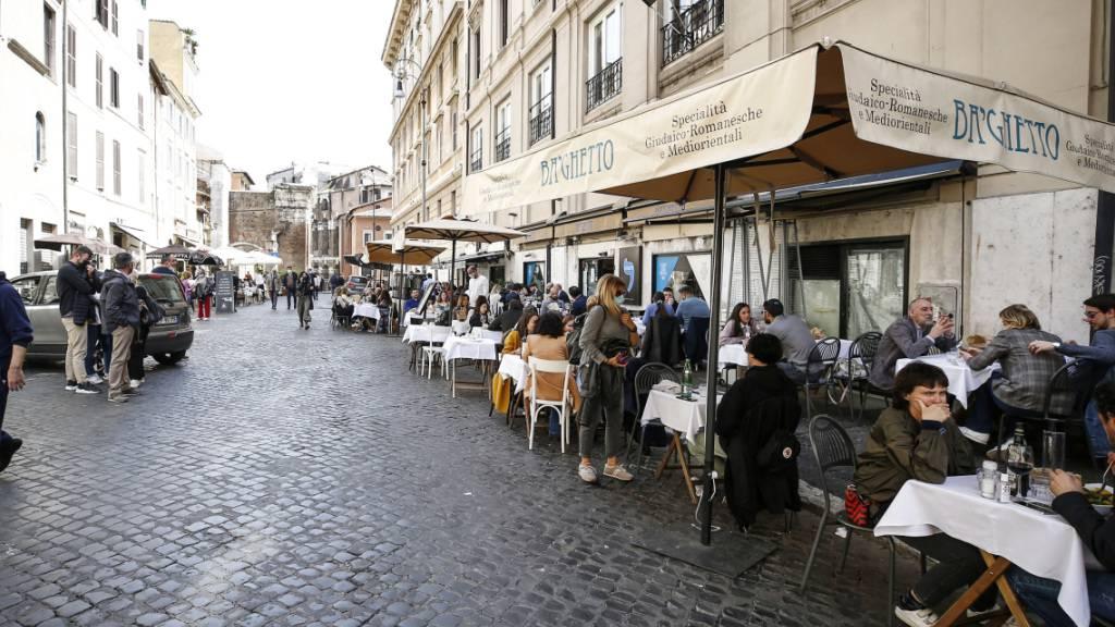 Menschen sitzen im Außenbereich eines Restaurants an Tischen. In Italien öffnen Restaurants und Bars in vielen Regionen wieder ihre Außengastronomie und Kulturstätten empfangen wieder Besucher. Foto: Cecilia Fabiano/LaPresse via ZUMA Press/dpa