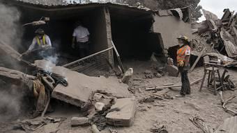 Feuerwehrleute suchen in mit Asche zugedeckten Trümmern nach Opfern des Vulkanausbruchs in der guatemaltekischen Ortschaft Escuintla.