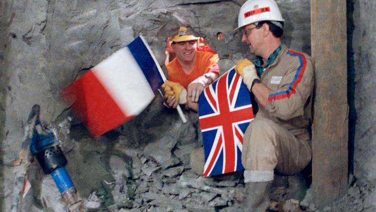 Am 1. Dezember 1990 reichen sich französische und britische Arbeiter durchs Durchbruchloch die Hand. Vier Jahre später wird der Eurotunnel eingeweiht.