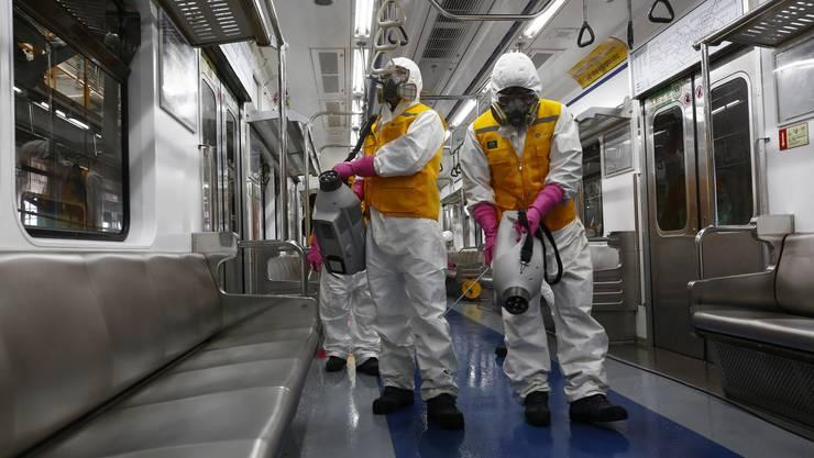 In Schutzanzügen reinigen Arbeiter eine U-Bahn in Südkorea.