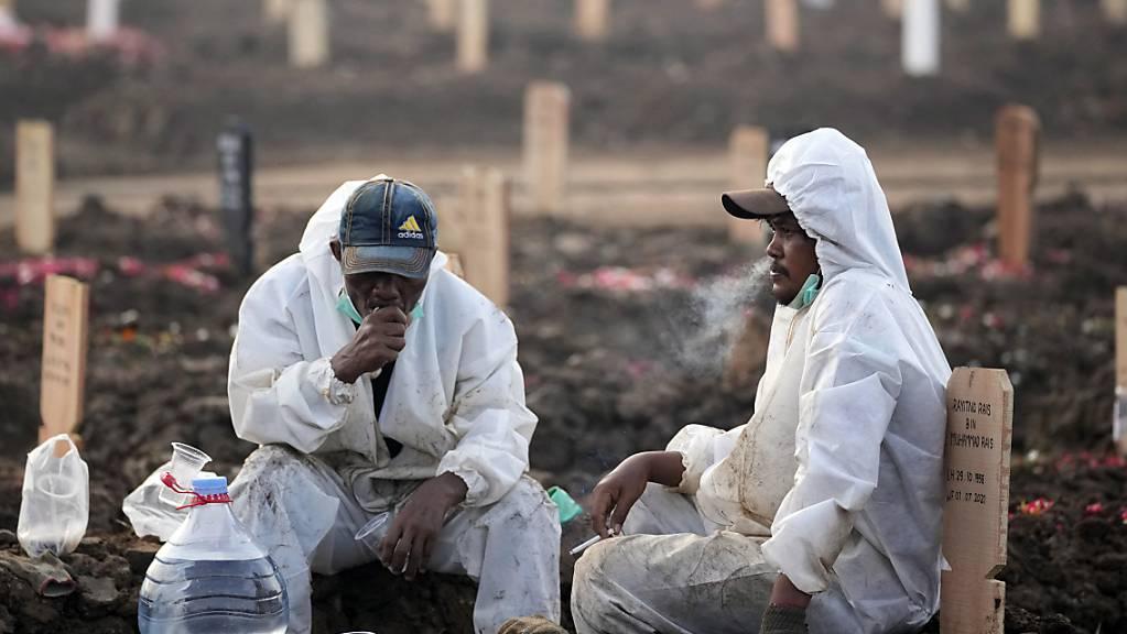 Mitarbeiter des Rorotan-Friedhof, welcher für Coronatote reserviert ist, tragen Schutzkleidung und sitzen während einer Pause zwischen den Gräbern.