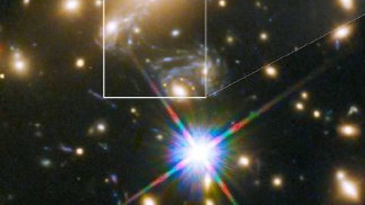 In rund fünf Milliarden Lichtjahren Entfernung von der Erde dient eine Ansammlung von Galaxien als Gravitationslinse. Dies lässt den Stern Ikarus sichtbar werden, der neun Milliarden Lichtjahre entfernt ist.