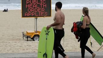 Ein Schild weist Menschen an einem Strand in Sydney auf Einschränkungen hin. Foto: Mark Baker/AP/dpa