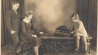 Roger und Lily Kuriger beobachten ihre Schwester, die kleine Irène, wie sie das Urtier aus Holz der Staader Eiche «füttert»