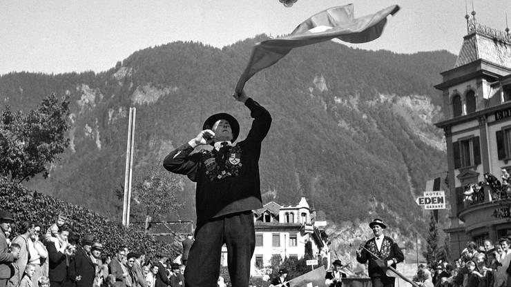 Unter den Augen von zahlreichen Zuschauern zeigt ein Fahnenschwinger am 22. September 1946 anlaesslich des Schweizerischen Trachten- und Alphirtenfests in Unspunnen beim Festumzug durch die Stadt Interlaken sein Koennen. Das erste Unspunnenfest fand 1805, unweit der Ruine Unspunnen, statt. Das Unspunnenfest feiert dieses Jahr seinen 200. Geburtstag. Neben dem Stossen des Unspunnensteins, sich im Schwingen messen, wird in schmucken Trachten getanzt, musiziert und gejodelt.
