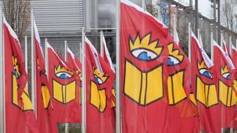 Fahnen mit dem Logo der Leipziger Buchmesse wehen am Leipziger Messegelände. Etwa 2600 Aussteller präsentieren sich bis zum 18. März. Bei der Eröffnung am Mittwoch wurde zu Toleranz gegenüber rechten Verlagen aufgerufen.
