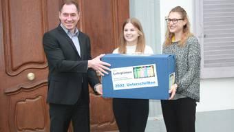 Saskia Olsson (r.) und Alina Isler von der Starken Schule Baselland überreichen Landschreiber Peter Vetter die 2602 Unterschriften der Initiative, die klare Stoffinhalte für den Lehrplan fordert.