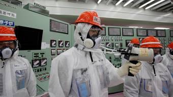 Mitarbeiter des AKW-Betreibers Tepco messen die Radioaktivität im Innern des Reaktors Fukushima Daiichi.