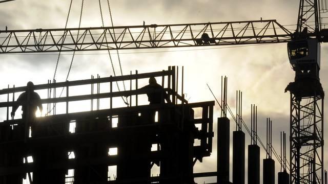 Bauarbeiter ziehen ein Gebäude hoch (Symbolbild)