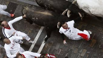 Stiere holen in den engen Gassen Pamplonas einen Läufer ein