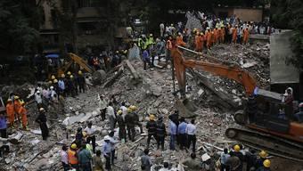 Helfer suchen in den Trümmern des eingestürzten Hauses nach Verschütteten.