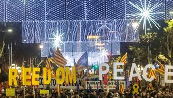 """Inmitten der protestierenden Menge am Freitagabend in Barcelona wurden mit riesigen Buchstaben die Worte """"Freiheit"""" und """"Frieden"""" gebildet."""