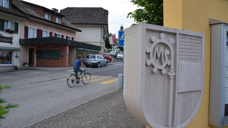Blick Richtung Gemeindehaus (hinten mit Flagge). Im Vordergrund das Gemeindewappen in Stein auf dem Lindenplatz.