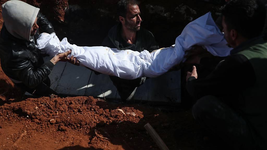 Syrische Männer tragen während einer Beerdigung auf einem Friedhof den Leichnam einer Person, die bei einem Raketenangriff auf ein Krankenhaus getötet wurden. In Syrien sind bei einem Angriff von Regierungstruppen auf ein Krankenhaus nach Angaben von Menschenrechtlern mindestens fünf Menschen getötet worden. Foto: Anas Alkharboutli/dpa