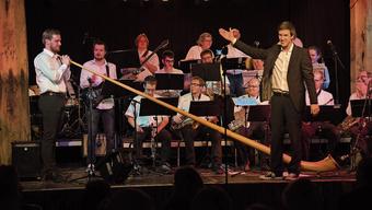 Reto Anneler (r.) präsentiert die Big-Band der Fachhochschule Nordwestschweiz (FHNW) mit einem Alphornspieler.